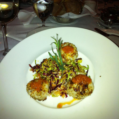 Sea scallops, brussels sprouts salad drizzled with red peppers vinaigrette